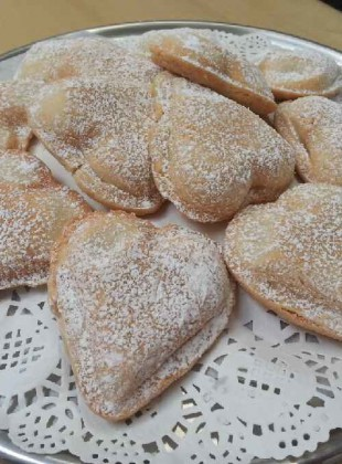 Friable shortbread cookie heart filled with homemade vanilla cream with organic vanilla bean and then dusted with confectioner sugar