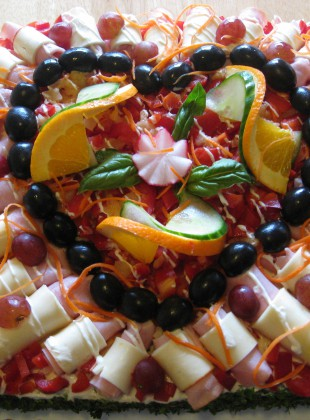 A savory cake with an array of cold cuts and cheese